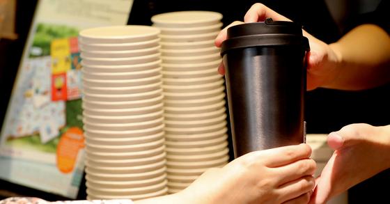서울 소공동의 한 커피전문점에서 한 고객이 텀블러에 든 음료를 받고 있다. 뉴스1