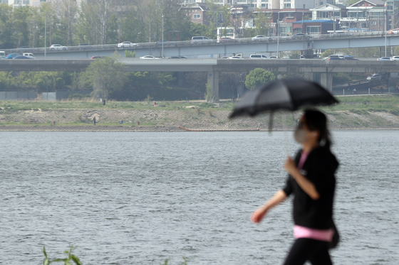 강한 햇빛이 내리쬐며 21일 전국의 낮 기온이 최고 29도까지 오른다. 서울의 낮 최고기온 23도를 기록한 20일 오후 한 시민이 내리쬐는 햇빛을 가리기 위해 가림막을 쓰고 한강공원을 지나고 있다. 뉴스1