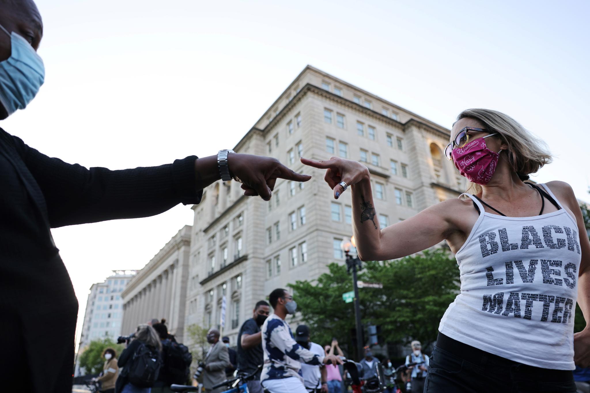 데릭 쇼빈에 대한 평결이 전해진 20일 백인 여성과 흑인 남성이 미국 워싱턴 DC BLM 광장에서 손가락을 마주 대고 있다. 로이터=연합뉴스