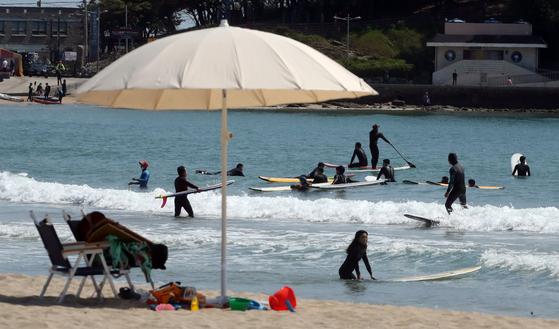 지난 11일 부산 해운대구 송정해수욕장 백사장에 등장한 파라솔 뒤로 시민들이 시원하게 서핑을 즐기고 있다. 송봉근 기자