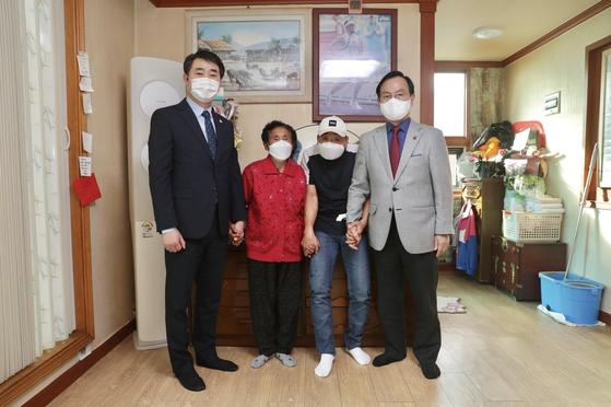박상돈 천안시장(오른쪽)과 한남교 천안시체육회장(맨 왼쪽)이 지난 21일 이봉주 집을 찾아 성금을 전달하고 격려했다. 사진 천안시