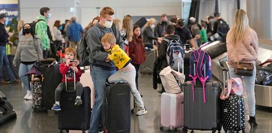 지난 3월17일 미 솔트레이크시티 국제공항에서 여행객들이 짐을 옮기고 있다. 국제 통계사이트 아워월드인데이터에 따르면 21일 기준 미국인 40.2%가 1회 이상 접종, 완전 접종자 비율은 26.2%를 기록했다.[AP=뉴시스]