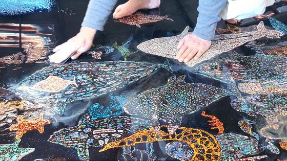 옻은 원래 색깔이 없다. 여기에 천연 염료를 녹여 넣어 옻칠을 한다. 옻칠한 삼베 위에 그려진 나전의 색색이 무척 아름답다. 성파 스님의 작품은 한반도에 깃들어 있는 고대사의 생생한 기록을 선명하게 보여준다는 측면에서도 의미가 깊다.