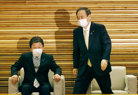 스가 요시히데 일본 총리(오른쪽)가 23일 오전 일본 총리관저에서 각의에 임하고 있다.   스가 총리는 이날 오후 열리는 신종 코로나바이러스 감염증(코로나19) 대책본부회의에서 도쿄 등에 대한 코로나19 긴급사태선언 발령을 결정한다. [교도=연합뉴스]