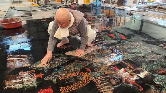 성파 스님이 맨발로 반구대 암각화 작품 위에 올라가 작업을 하고 있다. 우주에 띄워진 그림의 색상이 선명하다.