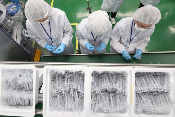 문재인 대통령이 지난 2일 18일 오후 전북 군산시 코로나19 백신접종용 최소잔여형(LDS) 주사기 생산시설인 풍림파마텍을 방문했다. 당시 생산라인에서 관계자들이 작업을 하고 있다. [청와대사진기자단]
