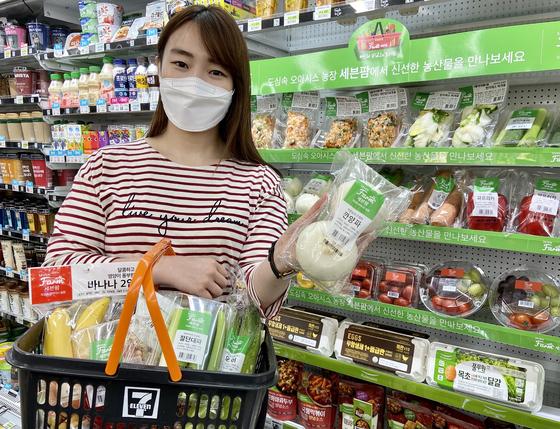 편의점 점포 직원이 깐 양파 상품을 들어보이고 있다. [사진 세븐일레븐]