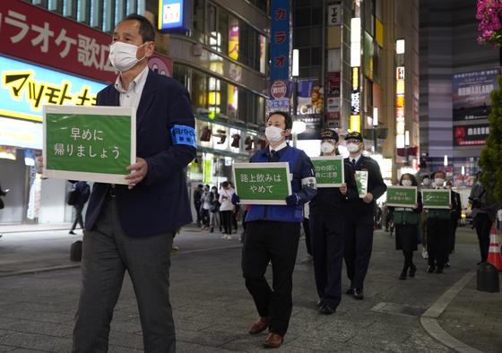 23일 도쿄 지하철 직원들과 경찰이 3차 긴급사태 선언을 앞두고 빠른 귀가를 호소하는 피켓을 들고 신주쿠 가부키초를 행진하고 있다. [EPA=연합뉴스]