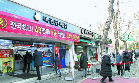 '로또 명당'으로 알려진 서울 노원구의 한 복권판매점 앞에 시민들이 로또를 사기 위해 줄을 서 있다. [뉴시스]