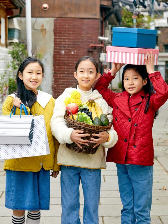 왼쪽부터 김준효(서울 원촌초 5) 학생모델·이수정(경기도 소하초 5)·박하윤(경기도 서원초 4) 학생기자가 비대면 시대의 새로운 문화로 떠오른 '하이퍼로컬' 서비스를 상징하는 소품을 각각 들고 포즈를 취했다,