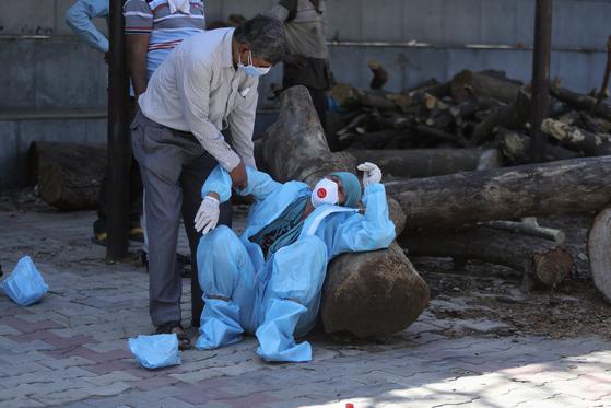 25일(현지시간) 인도 잠무에서 신종 코로나바이러스 감염증(코로나19)에 친족을 잃은 한 인도인이 장례식 중 슬퍼하고 있다. [AP=연합뉴스]