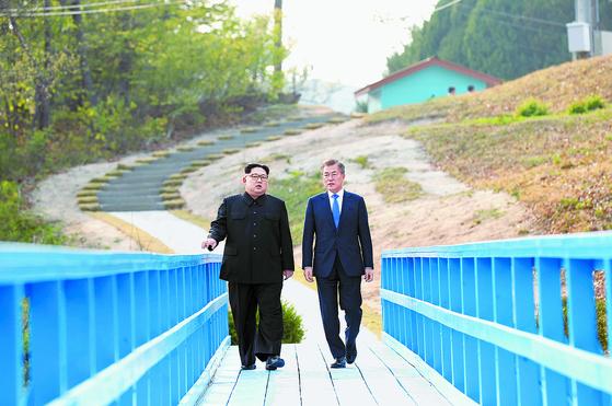 문재인 대통령(오른쪽)과 김정은 국무위원장이 공동 식수를 마친 후 군사분계선 표식물이 있는 '도보다리'까지 산책을 하며 담소를 나누고 있다. [청와대사진기자단]