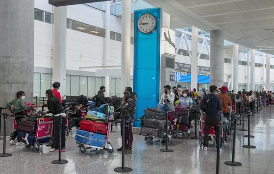 23일(현지시간) 뉴델리에서 출발한 비행기를 타고 캐나다로 입국한 승객들이 토론토 공항에서 격리 호텔에 들어가기 위해 긴 줄을 서 있다. 캐나다에서는 인도와 파키스탄발 비행기 탑승객에 대한 입국을 제한하고 있다. AP=연합뉴스