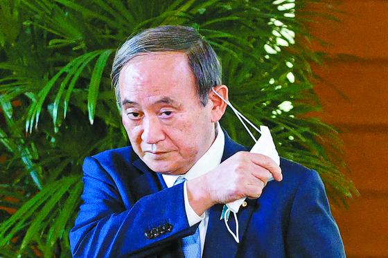 일본 자민당이 재·보선에서 전패한 26일 스가 요시히데 총리가 기자들의 질문에 답변하기 위해 마스크를 벗고 있다. [AP=연합뉴스]