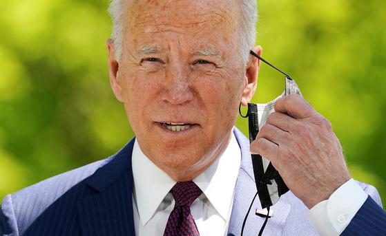 조 바이든 미국 대통령이 27일 백악관 잔디밭에서 마스크를 벗고 있다. CDC는 이날 백신 접종자의 경우 실외에서 소규모로 모일 때는 마스크를 벗어도 된다는 새로운 지침을 내놓았다. [로이터=연합뉴스]