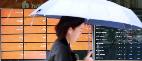 암호화폐 과세 등을 둘러싼 젊은 층의 분노가 확산하자 정치권도 대안 마련에 부심하고 있다. 사진은 2018년 5월 6일 오후 서울 중구의 한 가상화폐거래소 앞에서 우산을 쓴 시민이 오가는 모습. 연합뉴스