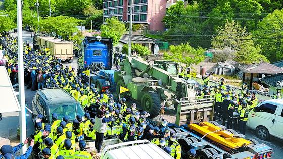 28일 고고도미사일방어(THAAD·사드) 기지 인근의 경북 성주군 소성리 마을회관 앞 도로에서 군용 장비를 실은 트럭이 기지로 진입하고 있다. [뉴스1]