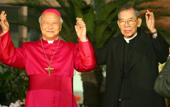 지난 2006년 2월 22일 로마 교황청으로부터 추기경으로 임명 받은 정진석 추기경(왼쪽)이 명동성당에서 진행된 기자회견에서 김수환 추기경과 손을 맞잡고 기쁨을 나누는 모습. 연합뉴스