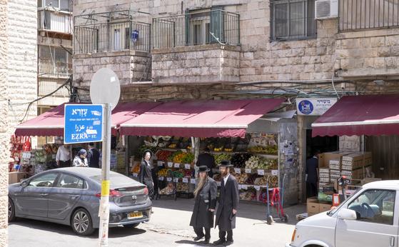 29일(현지시간) 이스라엘 예루살렘 게울라(종교인 마을) 지역에서 검은색 유대교 정장을 입은 사람들이 식료품 가게 앞을 지나고 있다. 임현동 기자