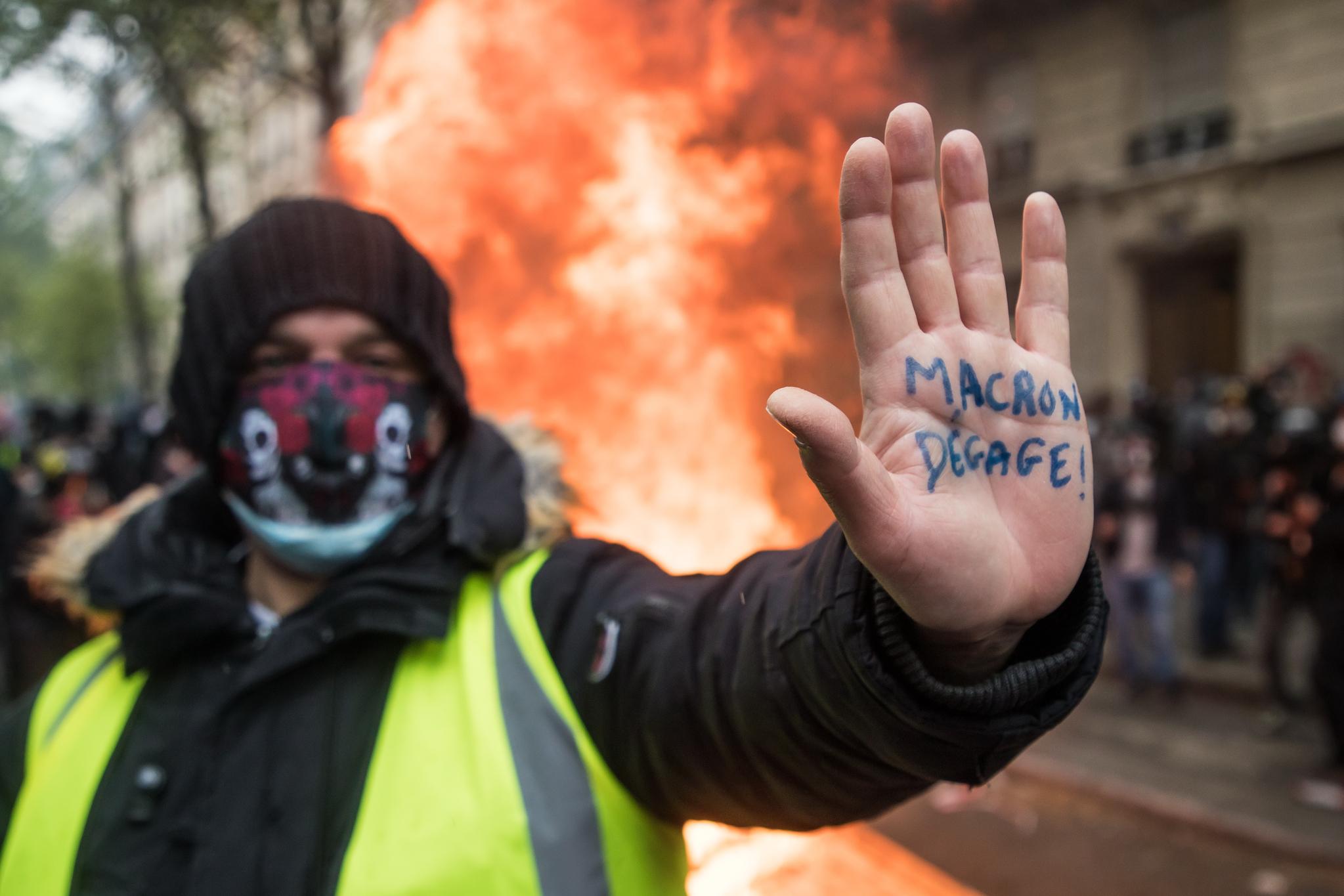 """프랑스의 '노란 자켓' 시위대가 노동절인 1일(현지시간) 파리에서 집회를 하며 """"(대통령)마크롱을 치워버려""""라고 쓴 글씨를 보여주고 있다. EPA=연합뉴스"""