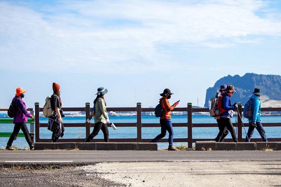 제주를 찾은 관광객들이 올해 1월 서귀포시 성산일출봉을 바라보며 제주올레길을 걷고 있다. 사진 제주올레