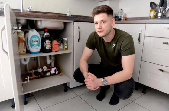 영국 청년 애슐리 더글라스가 배관 수리를 받은 자신의 집 싱크대 옆에 앉아 있다. [트위터 캡처]