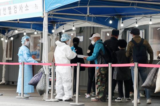 4일 오후 서울 중구 서울역광장에 마련된 신종 코로나바이러스 감염증(코로나19) 임시선별진료소에서 시민들이 검사를 받기 위해 줄을 서 있다. 뉴스1