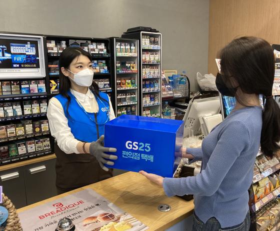 고객이 GS25 직원에게 접수한 '반값 택배'를 건네고 있다. [사진 GS리테일]
