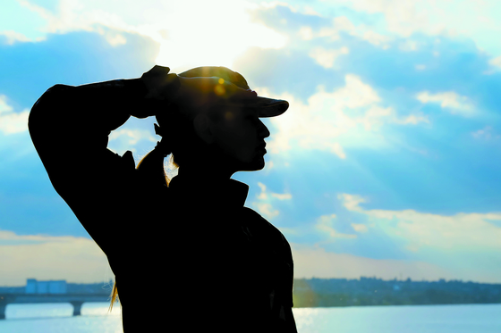 Female soldier in uniform saluting outdoors. Military service [Shutterstock]