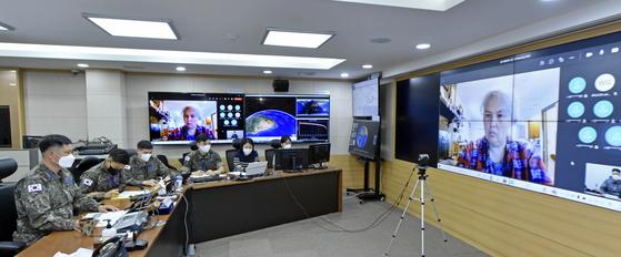 공군 우주정보상황실장 최성환 중령과 우주분야 임무요원들이 중국 창정 5B 로켓 잔해 추락에 대비해 미국 우주사령부 연합우주작전센터와 공조 화상회의를 열고 있다.  공군