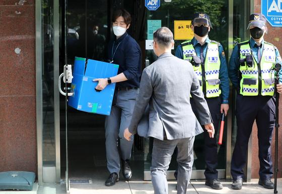 경찰 관계자들이 지난 6일 오후 박상학 자유북한운동연합 대표의 사무실에 대한 압수수색을 마친 뒤 압수품을 들고 나오고 있다. 연합뉴스