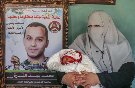 팔레스타인 출신의 모함마드 쿠드라(왼쪽 사진 속 남성)와 그의 아내 이만 쿠드라(오른쪽 여성)는 올해 시험관아기 시술을 통해 아들을 얻었다. 이들처럼 최근 몇몇 팔레스타인 여성들이 수감 중인 남편의 정자를 받아 시험관아기를 출산하는 사례가 있다고 AFP통신이 보도했다. [AFP=연합뉴스]