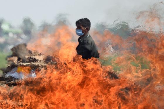 최근 인도에서 하루 코로나 확진자가 40만명을 넘기고 있는 가운데 지난 8일 인도에서 한 노동자가 코로나 사망자들의 시신을 화장하고 있는 모습. [AFP=연합뉴스]