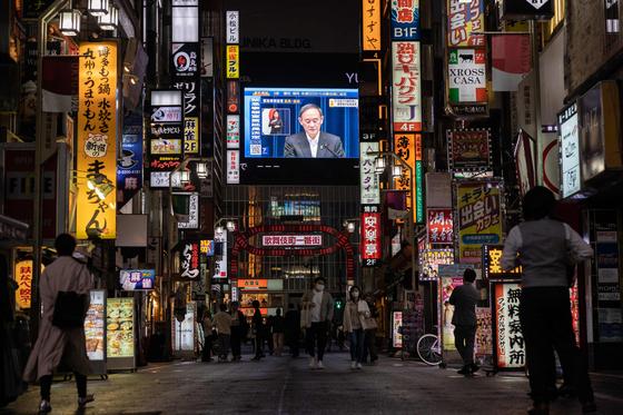 7일 일본 도쿄 신주쿠에서 시민들이 스가 요시히데 총리의 긴급사태 연장 기자회견 장면을 보며 거리를 지나고 있다. [AFP=연합뉴스]