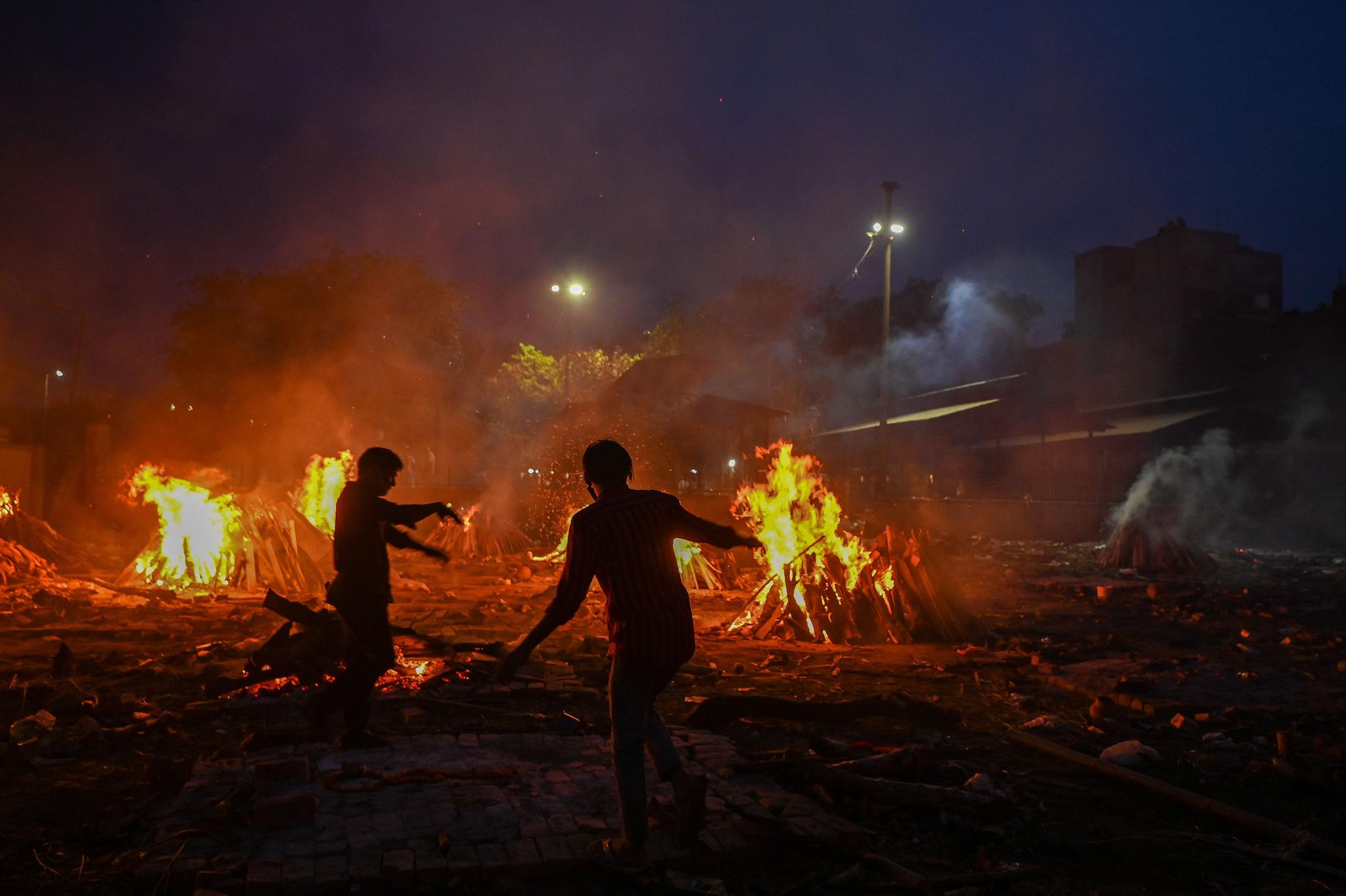 6일(현지시간) 인도 뉴델리의 한 화장장에서 자원봉사자들이 코로나바이러스로 사망한 사람들의 장례를 돕고 있다. AFP