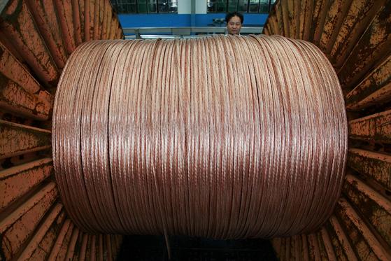 지난 2006년 중국 장쑤성 바오잉시의 한 전기 케이블 공장에서 직원이 구리선을 정리하고 있다.[로이터=연합뉴스]