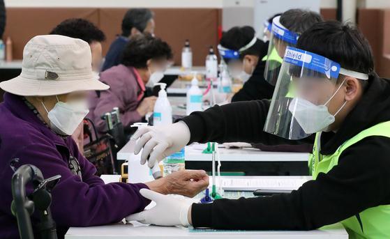 7일 오후 서울 관악구 코로나19 예방접종센터에서 접종 대상자가 백신(화이자) 접종에 앞서 발열 체크를 하고 있다. 뉴스1