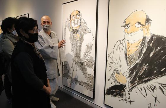 달마도 대가인 법용스님의 개인전이 열린 11일 부산 동구 부산시민회관 제1전시실을 찾은 관람객들이 코로나19 종식을 기원하는 마스크 쓴 달마도 작품을 감상하고 있다. 송봉근 기자