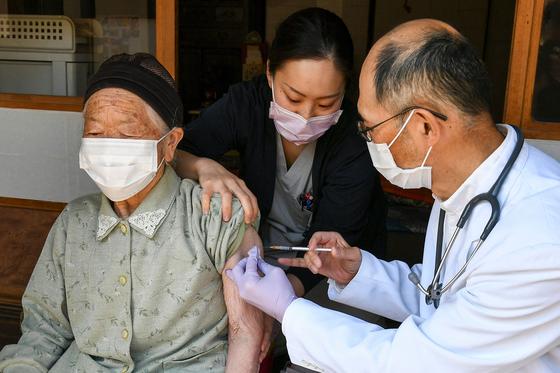 지난달 21일 일본 나가노현 기타아이키 마을에서 의료진이 가정을 방문해 노인에게 코로나19 화이자 백신을 접종하고 있다. [AFP=연합뉴스]