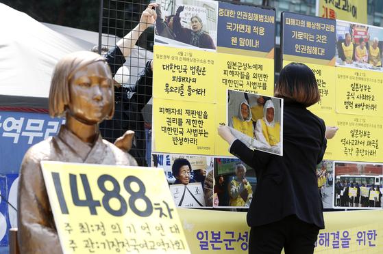 일본군 위안부 피해자들이 일본 정부를 상대로 낸 2차 손해배상 청구 소송에서 패소한 21일, 서울 종로구 일본대사관 앞에서 열린 제1488차 일본군성노예제 문제해결을 위한 정기 수요시위 기자회견을 앞두고 정의기억연대(정의연) 관계자들이 사법부를 규탄하는 문구를 부착하고 있다. [뉴시스]