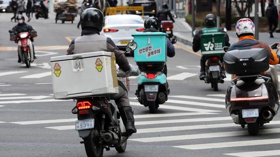 지난 3월 2일 서울시내에서 오토바이 기사들이 음식을 배달하고 있다. 이날 통계청에 따르면 온라인 주문 배달 음식 시장이 3년 새 6배 이상 커졌다. 온라인 주문 음식서비스 거래액은 지난해 17조4천억원으로 전년보다 78.6% 늘었다. 2017년 2조7천억원과 비교하면 6.4배 수준이다. [연합뉴스]