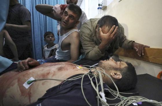 10일(현지시간) 가자지구에서 이스라엘과 팔레스타인 무장정파 하마스의 충돌이 빚어진 가운데 병원에 옮겨진 남성 앞에서 비통해하는 이들의 모습 [AP=연합뉴스]