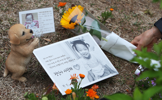 4일 오후 경기도 양평군 하이패밀리 안데르센 공원묘원에서 한 시민이 양부모의 학대로 생후 16개월 만에 사망한 정인 양을 추모하며 해바라기를 놓고 있다. 연합뉴스