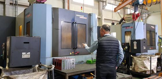 창원 두산중공업 협력업체에 근무하는 60대 근로자가 기계 작동 과정을 설명을 하고 있다. [중앙포토]