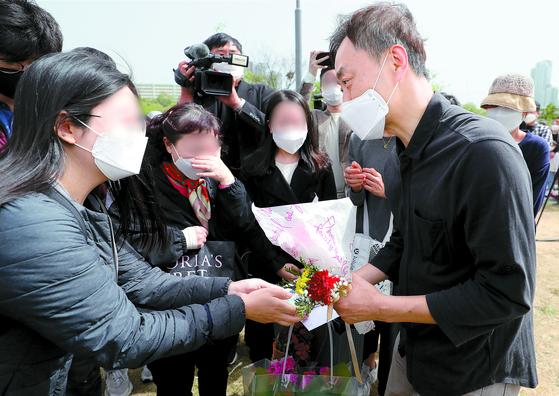 고(故) 손정민씨의 아버지 손현씨가 어버이날인 8일 반포한강공원 수상택시 승강장 앞에서 시민들로부터 카네이션을 받고 있다. [뉴스1]
