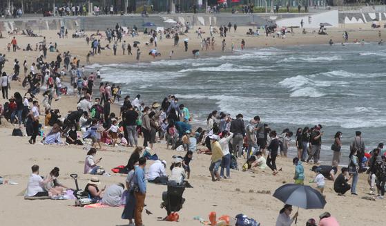 초여름 날씨를 보인 9일 부산 해운대해수욕장 백사장에 시민과 외국관광객들이 수영복 차림으로 선텐과 물놀이를 하며 더위를 식히고 있다. 송봉근 기자