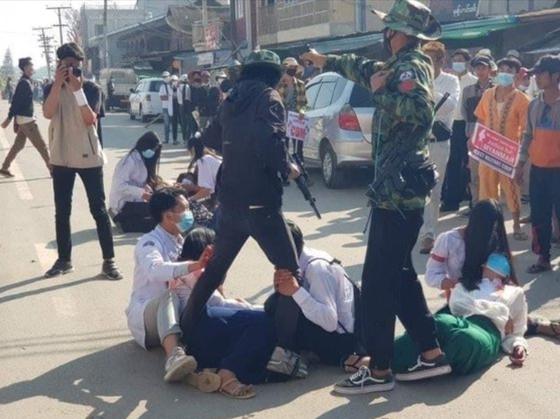 지난 2월 28일(현지시간), 첫 대규모 사상자가 나온 미얀마 '피의 일요일'의 한 장면. 부상자를 현장에서 돕던 의료진이 시민을 향해 총을 겨누는 군경의 다리를 붙잡고 총을 쏘지 말라고 애원하고 있다. [SNS 갈무리]