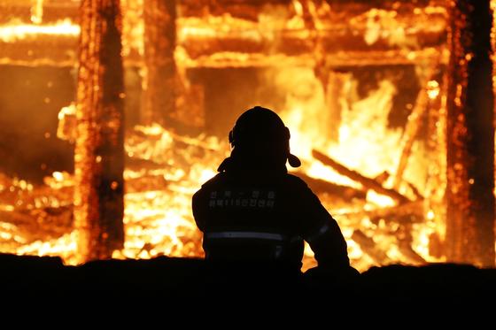 지난 3월 5일 오후 6시30분쯤 전북 정읍시 내장사 대웅전에서 방화로 추정되는 화재가 발생해 불길이 치솟고 있다. 한 소방관이 불길을 잡기 위해 안간힘을 쓰고 있다. 뉴스1