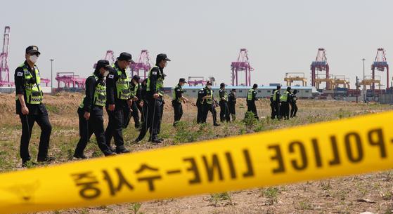 경찰관들이 12일 인천시 연수구 송도신항의 한 공터에서 4월 22일 인천 한 노래주점에서 실종된 A씨(40대)의 시신을 찾기 위해 수색하고 있다. 뉴스1