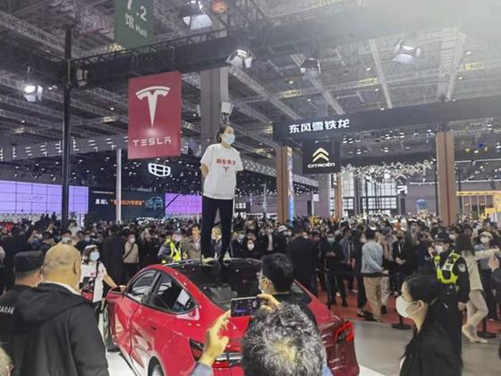 2021 상하이 모터쇼에서 한 여성이 테슬라 모델3 위에 올라가 항의하고 있다. [사진 바이두 캡처]
